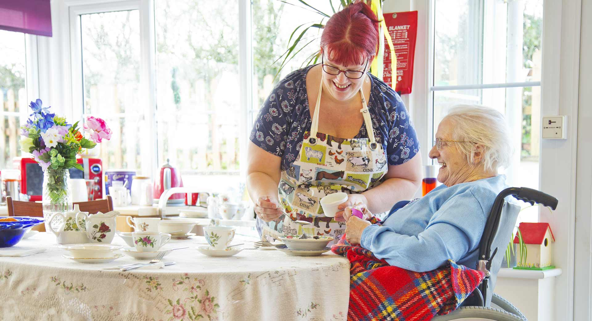 Staff and dementia care home resident baking together